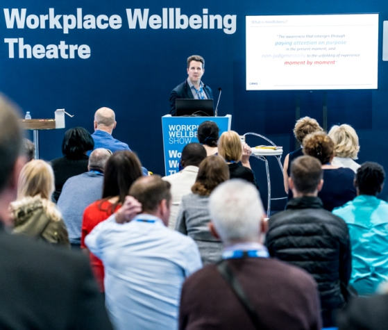 A speaker and audience  in the Workplace Wellbeing Theatre  in 2019