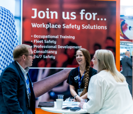 Three people in animated conversation on a stand at Safety & Health Expo 2019